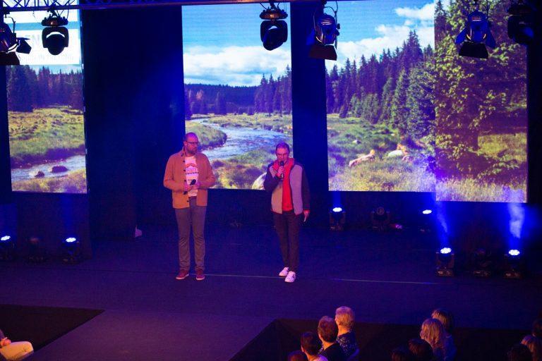 Moderatoren auf Buehne mit Videotechnik LED Screen im Hintergrund